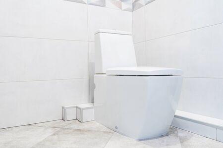 New modern ceramic toilet bowl near grey tiled wall in restroom.