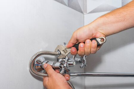 Plumber repairs a shower faucet in the bathroom.