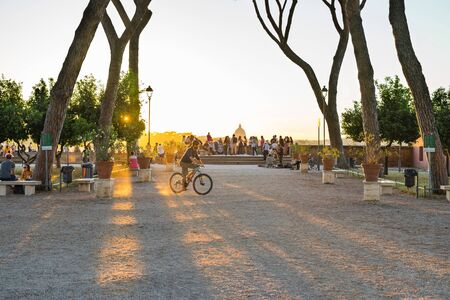 Rome, Italy - June 24, 2019: People enjoy sunset from the orange trees garden on the Aventine Hill with the view to Vatican.