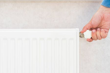 Male hand regulates the thermostat knob on the white heating radiator with at home a cold season.