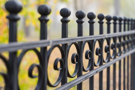 Beautiful decorative cast iron wrought fence with artistic forging. Metal guardrail close up. Stock Photo