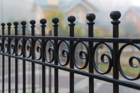 Beautiful metal fence on the background of houses in the fog in the autumn. Guardrail close up.