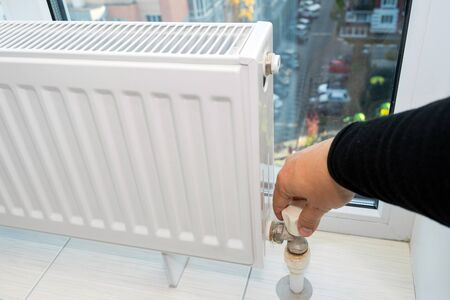 Hand adjusting the knob of heating radiator at home a cold season. Stockfoto