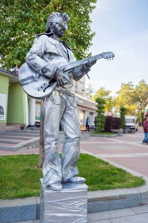 Irpin, Ukraine - September 21, 2019: Living statue rocker man with guitar is the entertainment for passerby.