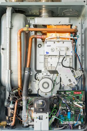 Kiev, Ukraine - October 03, 2019: Internal view of the gas water heater boiler for home heating. Installation, connection and maintenance concept.