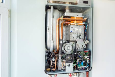 Kiev, Ukraine - October 03, 2019: View of the disassembled gas water heater boiler for home heating. Installation, connection and maintenance concept.