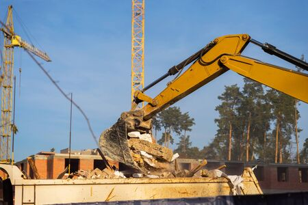 Details of excavator scoop destroying and loading debris into a dump truck. Construction background. Banco de Imagens