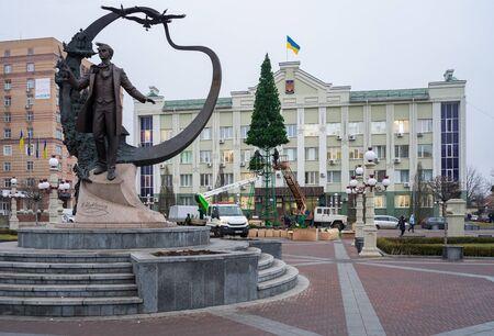 Irpin, Ukraine - December 10, 2019: Workers install the city main Christmas tree on the Tarasa Shevchenka Square. Banco de Imagens - 137983807
