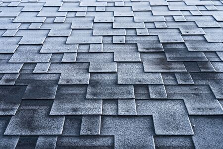 Asphalt roof shingles covered with frost with poorly insulated roofing construction. Banco de Imagens - 136794017