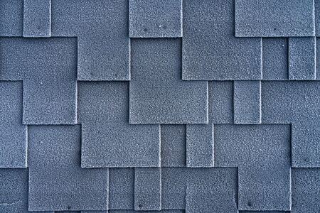 Close up view on asphalt roofing shingles covered with frost.