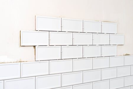 Unfinished white ceramic tiles with tile spacers. Concept of a kitchen renovation. Banco de Imagens