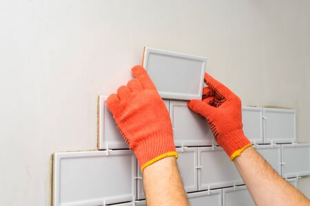 Worker is tiling the white tiles on the kitchen wall. Concept of a kitchen renovation. Banco de Imagens