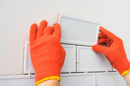 Contractor is tiling the white tiles on the kitchen wall. Concept of a kitchen renovation.