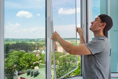 A contractor worker installing mosquito wire screen on house plastic windows to protect from insects. Standard-Bild
