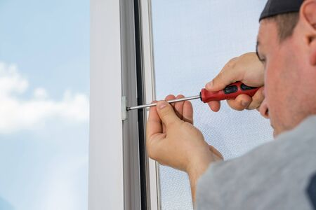 A contractor master adjusts and repair in house plastic windows. 版權商用圖片