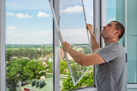 A worker installing mosquito wire screen on house plastic windows to protect from insects.