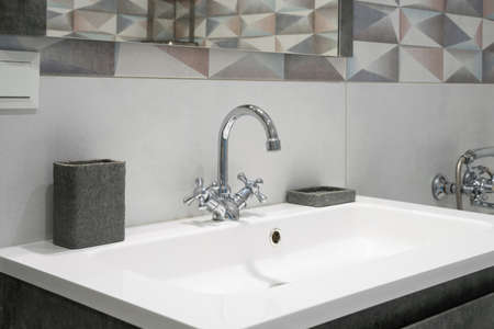 Modern bathroom interior with metal faucet and ceramic white sink. Bath accessories and mirror.