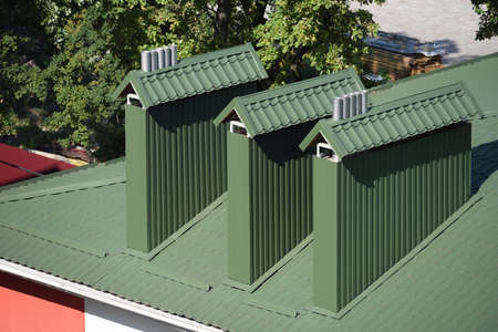 Green metal roof with big chimney pipes and ventilation system. 版權商用圖片