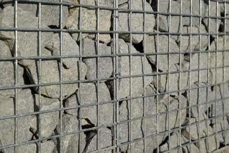 Decorative gabion fence is made of natural stone and metal mesh. 版權商用圖片