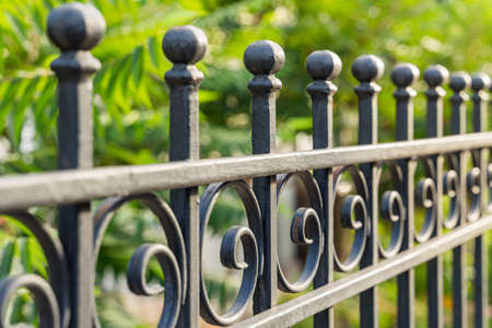 Beautiful decorative cast metal wrought fence with artistic forging. Iron guardrail close up.