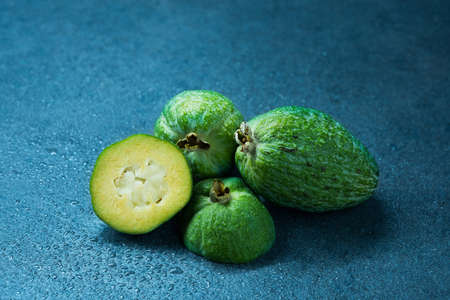 Tropical fruit feijoa (Acca sellowiana) on gray background. Healthy food.