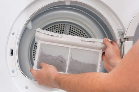 Man shows dust and dirt trapped by the after use clothes dryer filter.