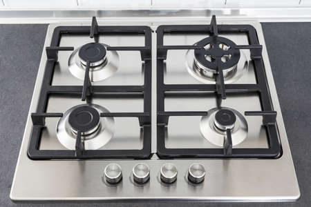 Closeup a gas stove burner and cast iron grate. Stainless steel kitchen surface. 스톡 콘텐츠
