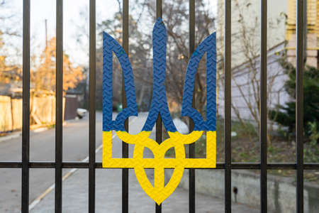 Coat of arms of ukraine in blue and yellow on a black metal fence. 스톡 콘텐츠