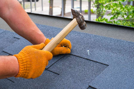 Worker hands installing bitumen roof shingles using hammer in nails. Banco de Imagens