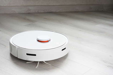A robot vacuum cleaner helps in cleaning an apartment or house. Banco de Imagens