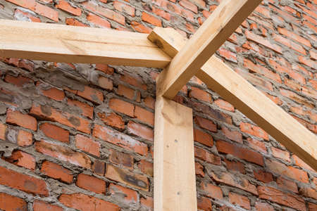 Closeup installation of wooden beams at construction the roof truss system of the house. Banco de Imagens