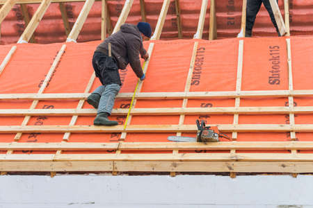 Irpin - Ukraine, March - 13, 2021: Roofing contractor takes measurements before installing roof boards and vapor barriers for metal tiles in winter time. Editorial