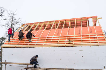 Irpin - Ukraine, March - 13, 2021: Roofing contractors installing roof boards and vapor barriers for metal tiles in winter time. Insulation of the facade of the house.