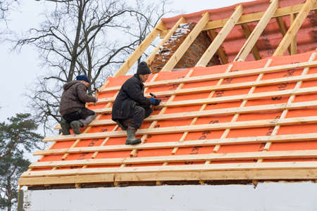 Irpin - Ukraine, March - 13, 2021: Roofing contractors installing roof boards and vapor barriers for metal tiles in winter time. Editorial