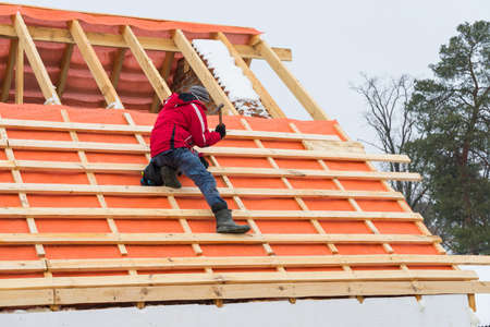 Roofing contractor installing roof boards and vapor barriers in winter time.
