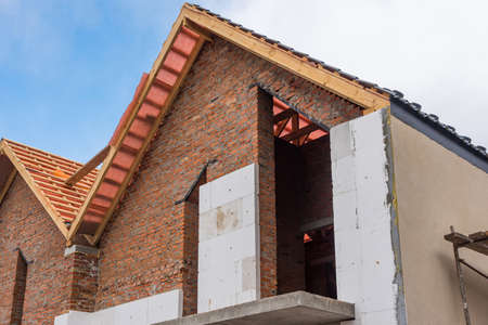 Unfinished house of brick, still under construction, installing roof, wall insulation. Banco de Imagens