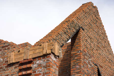 Brick house construction before installation of wooden beams at the roof truss system.