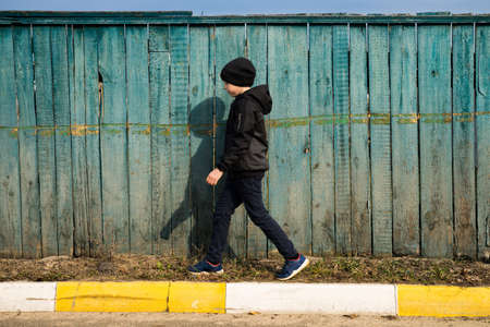 A child in motion walks along an old wooden fence. Photo of a person in dynamics. Banco de Imagens
