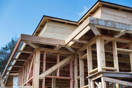 Installation of wooden beams at construction the roof truss system and frame of the house. Banco de Imagens