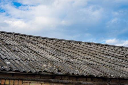 Old asbestos roof slates against blue sky