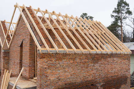 Installation of wooden beams at construction the roof truss system of the brick house. Mauerlat lying on monolithic frame.
