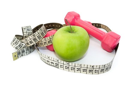 Dumbbells with green apple and measuring tape on white Stock Photo