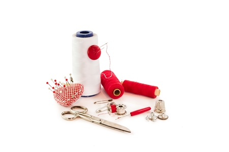 collection of sewing tools and supplies in a sewing kit on white