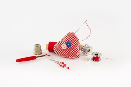 Red pincushion with sewing tools around it  Stock Photo