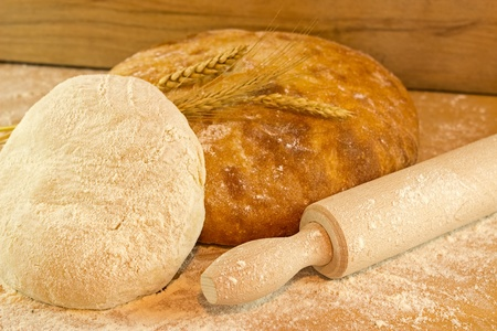 Freshly baked bread on wooden board with rolling pin