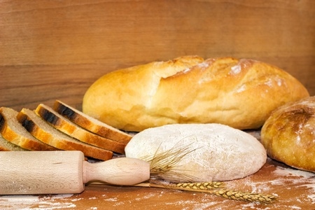 Baked baguette and bread on wooden board Stock Photo