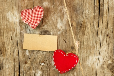 Red hearts and blank note on wooden background