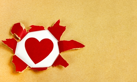 heart under: red paper heart under torn rustic paper