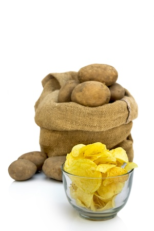 Delicious potato chips in a bowl with raw potatoes in background  Stock Photo