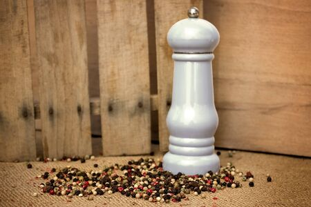 Colored peppers mix with pepper mill over vintage background  Stock Photo